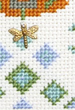 detail of cross stitch Fountain sampler kit with brass charm