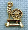 spinning wheel brass charm