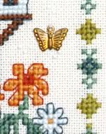 detail of Dovecote cross stitch kit with brass charm