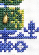 detail of Topiary Garden with ladybird charm cross stitch kit